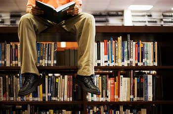 Image of person-sitting-on-book-shelf-in-library