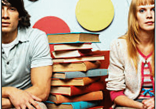 Two students sitting between books
